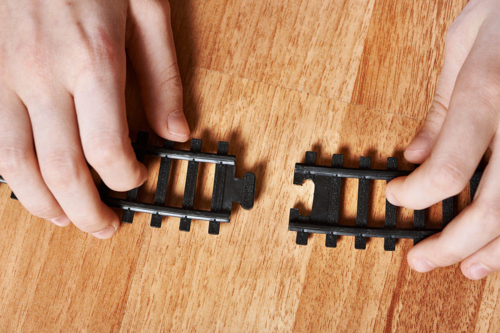 Kind verbindt twee stukken rails van speelgoedtrein