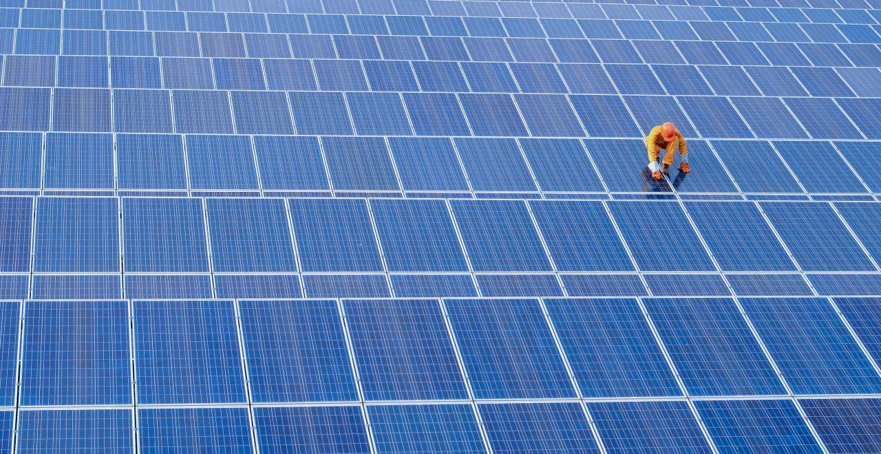 Bouwvakker op een dak van zonnepanelen