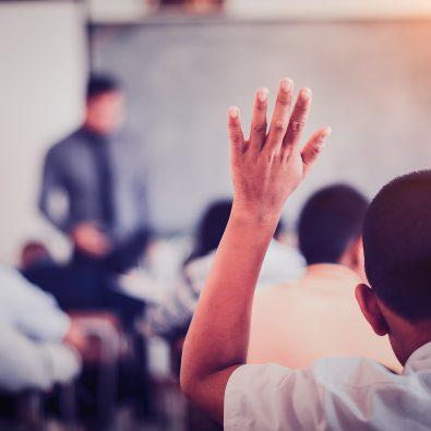 Kind steekt hand op in klaslokaal