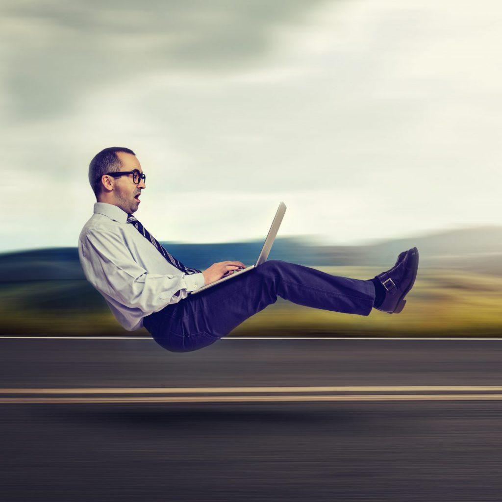 Man vliegend met laptop boven de snelweg