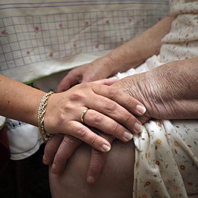 Jonge vrouw legt hand op knie van oude vrouw